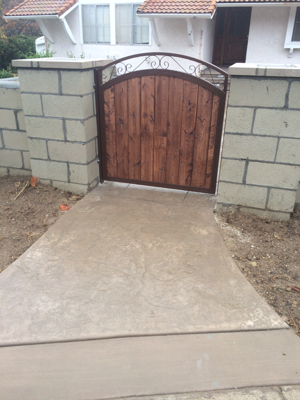 Concrete landscaping walk way to gate